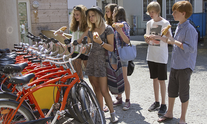 Teenage friends eating hotdogs and looking at bicycles