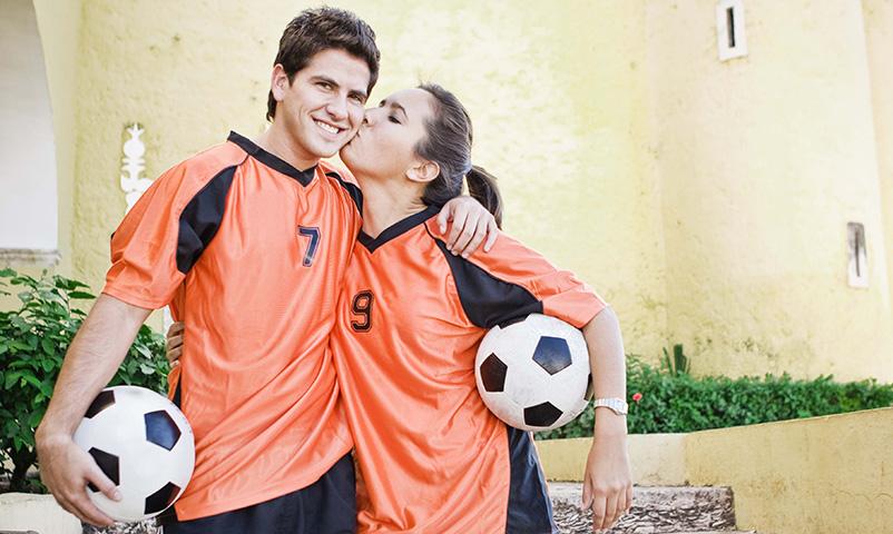 Woman kissing man wearing soccer jerseys holding soccer balls